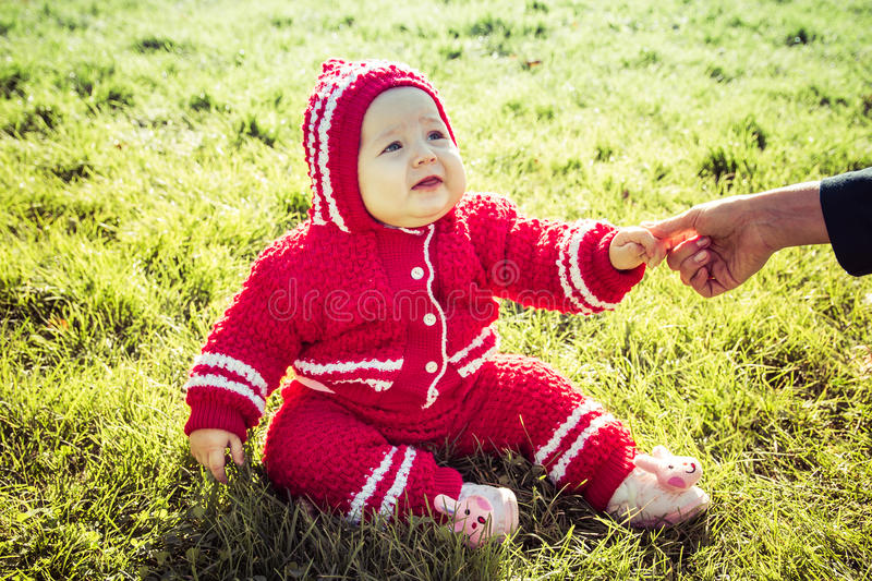 Little baby sitting on the grass. Mom holding the baby by the arm stock image