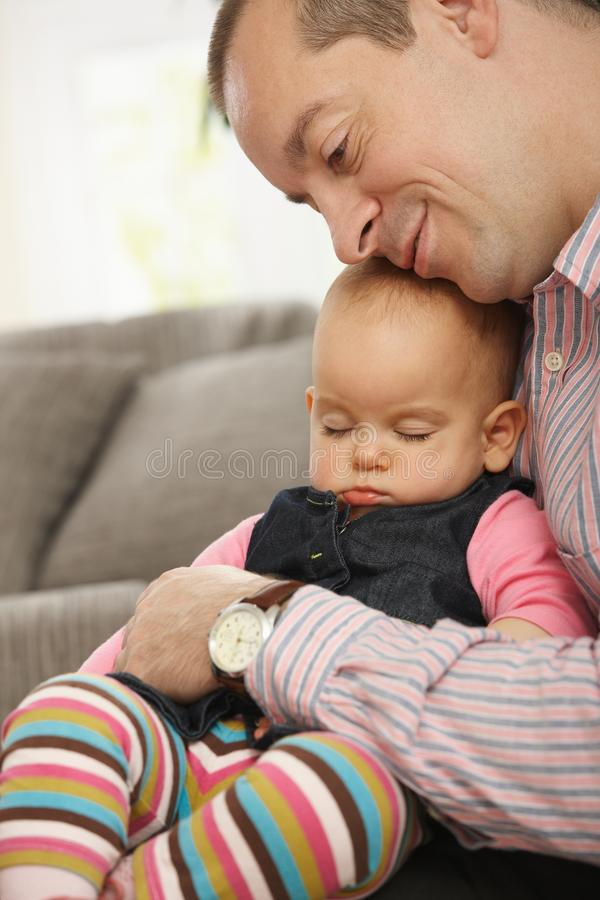 Little baby sleeping. Cute little baby sleeping held in father's arm at home stock photo