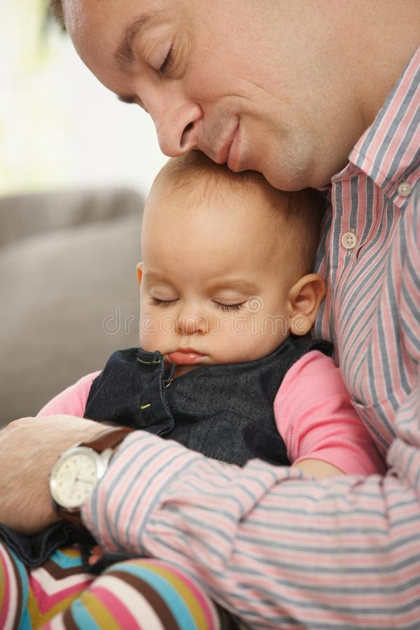 Little baby sleeping. Cute little baby sleeping held in father's arm at home royalty free stock photos