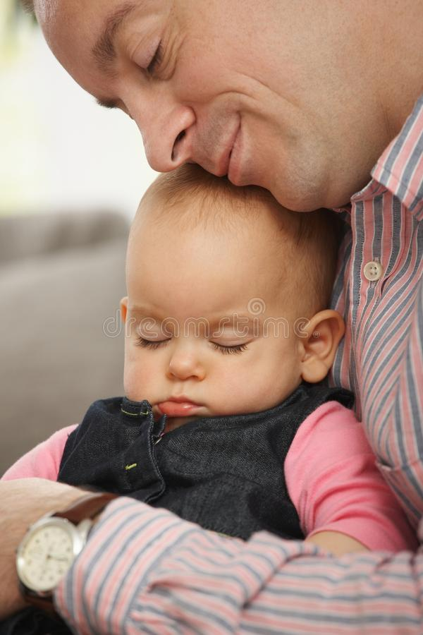 Little baby sleeping. Cute little baby sleeping held in father's arm at home royalty free stock photography