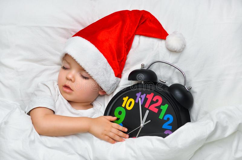 Little baby sleeping on white linen in the Santa hat and alarm show five minutes to eleven royalty free stock image