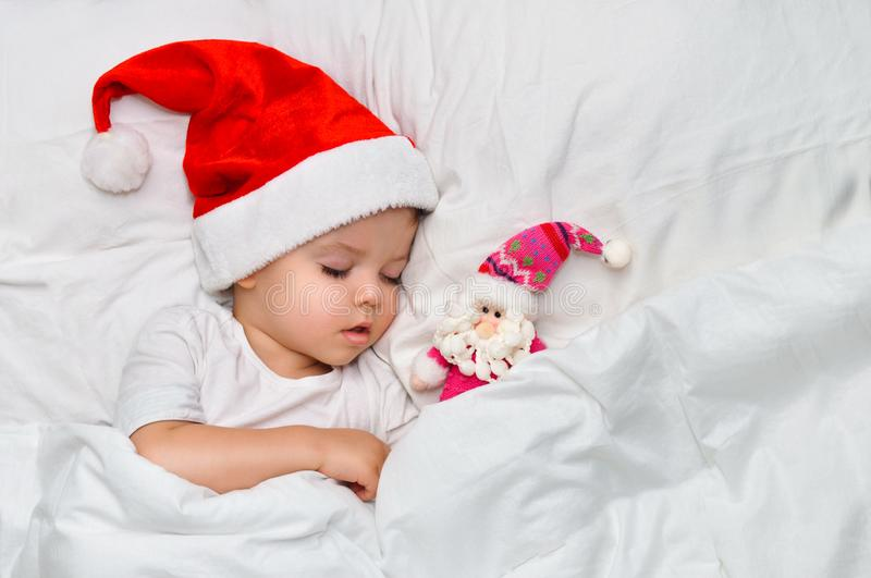 Little baby sleeping on white linen in the Santa hat with his toy Santa Claus. stock images