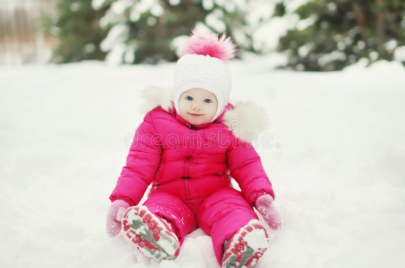 Little baby on the snow in the winter royalty free stock photo