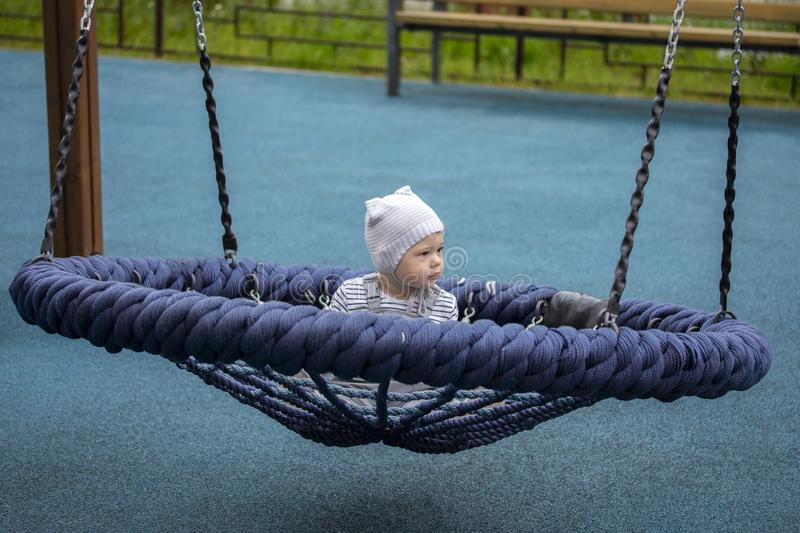Little baby on spider web nest swing. Baby girl boy 1 year swinging on a swing royalty free stock photo