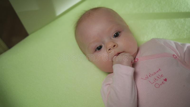 Lovely Baby Sucks Her Finger close-up. Little baby sucks hers fingers close-up royalty free stock photos