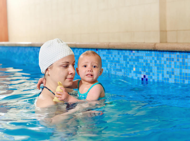 Little baby swimming. Adorable baby girl enjoying swimming in a pool with her mother, early development class for infants teaching children to swim stock photography