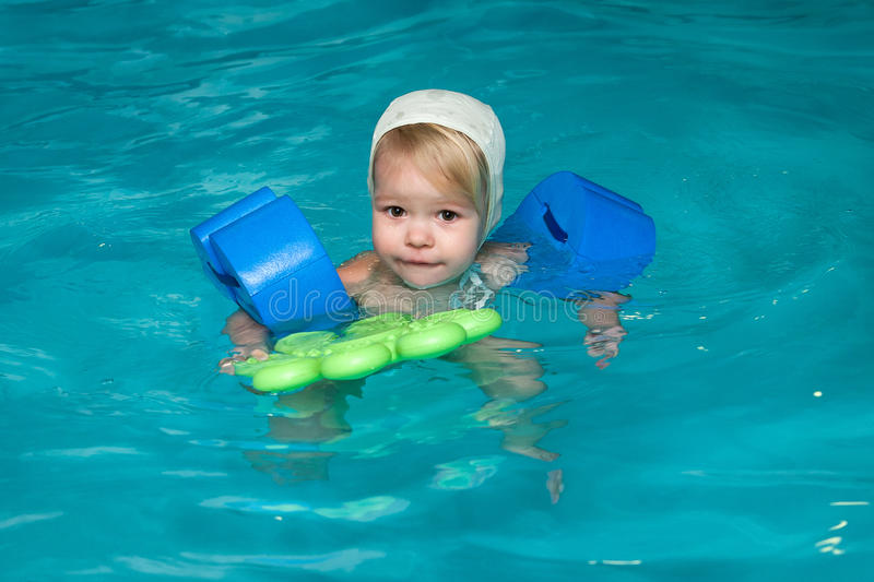 Little baby swimming in water. Little baby swimming in blue water stock images