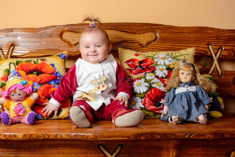 Little baby with a tail sits on a sofa with embroidered pillows and toys royalty free stock photography