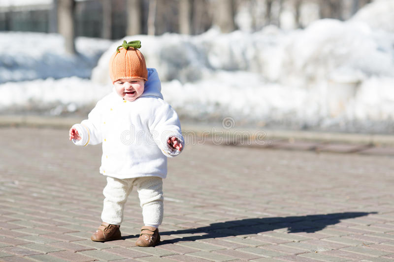 Little baby taking her first steps on sunny day royalty free stock image