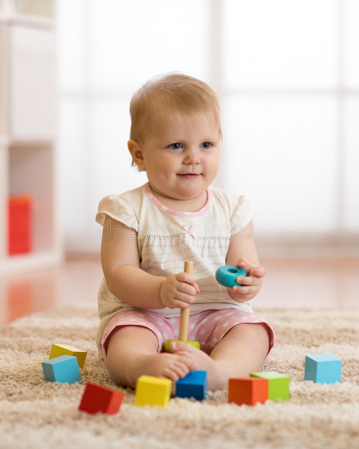 Adorable baby playing with colorful toy pyramid sitting on carpet in white sunny bedroom. Toys for little kids. Child stock photography