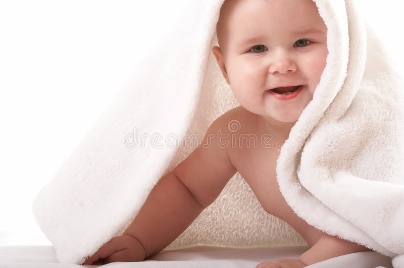 Little baby under white towel stock images