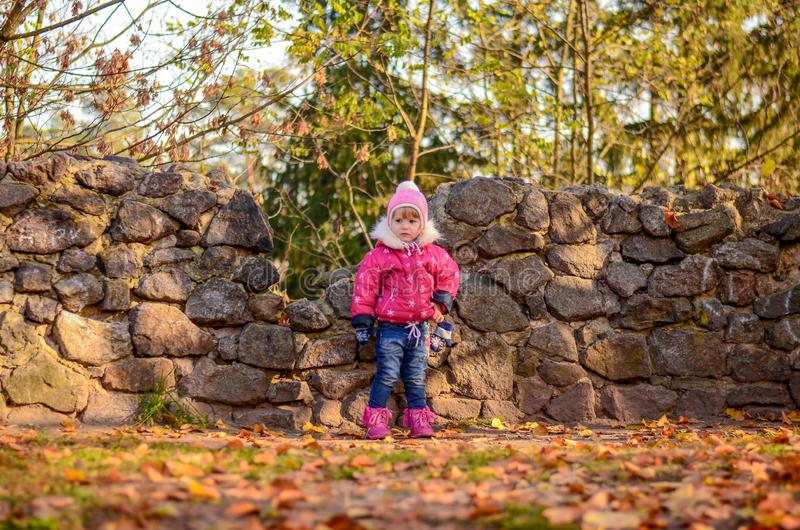 Little girl in winter clothes stands on stone wall background royalty free stock photo
