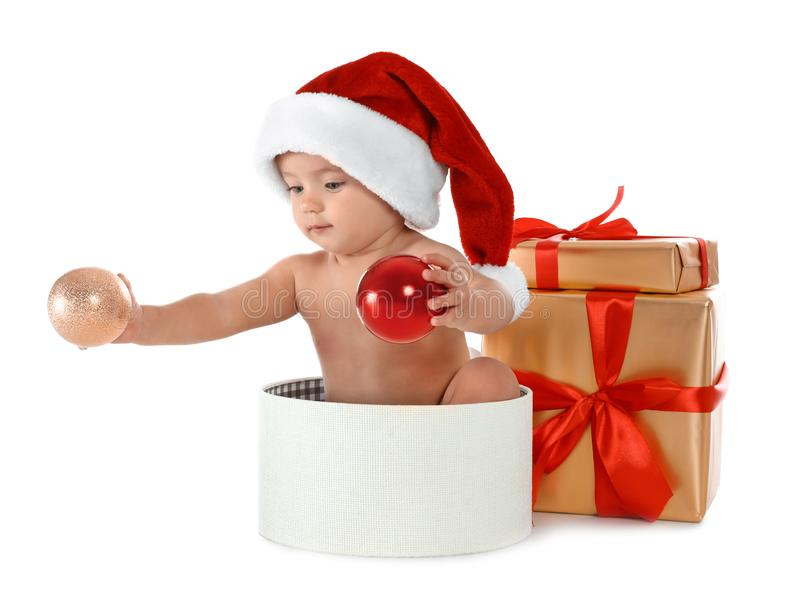 Little baby wearing Santa hat with Christmas gifts sitting in box on white background stock image