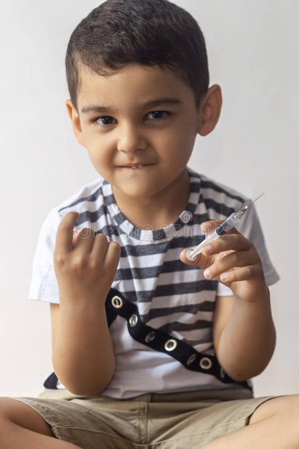 A little bad boy holding syringe and calling somone with his finger. A kid having fun at hospital. A little bad boy holding syringe and calling somone with his royalty free stock image