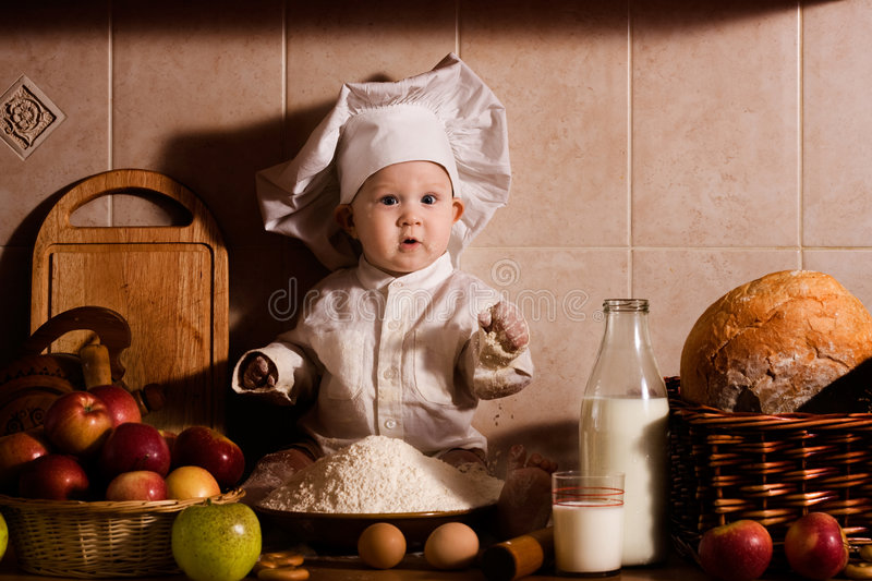 Little baker. Little boy in the cook costume at the kitchen sitting on the table. Special toned photo f/x stock photos
