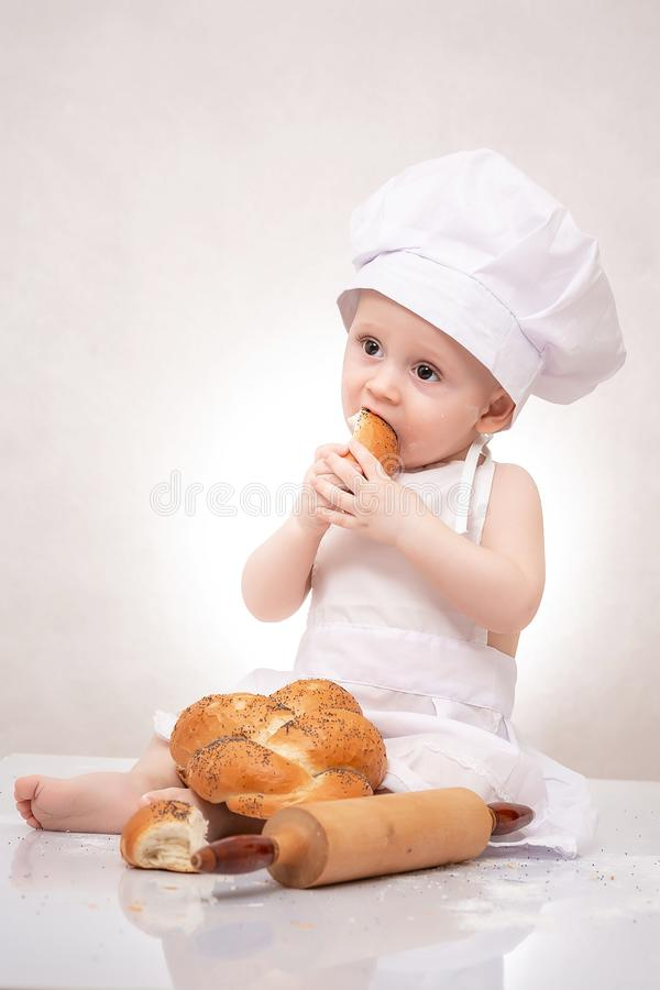 Little baker baby boy with loaf dressed in chef hat, laughing happily stock photo