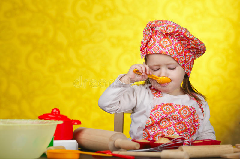 Little baker or cook girl cuts dough for cookies stock image