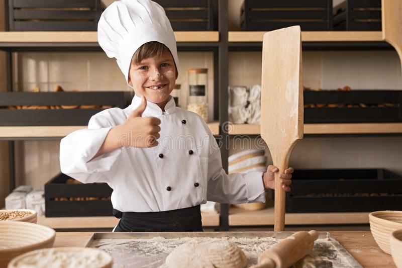 Little baker gesturing thumb up stock images