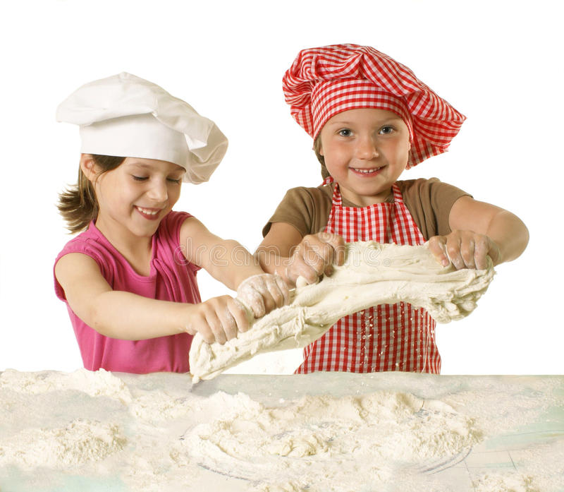 Little bakers. Little girls at the kitchen making bread dough stock photos