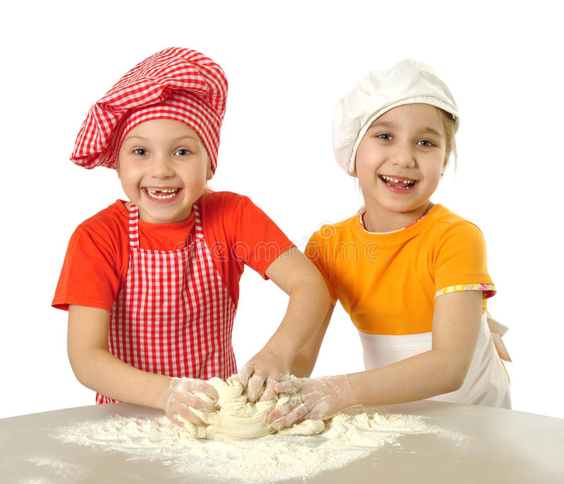 Little bakers. Two little girls making dough royalty free stock photography