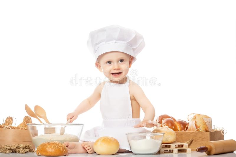 Little bakers in a suit of the cook surprised and smiling in the kitchen. Small kid as a little cook or scullion make pizza in royalty free stock photo