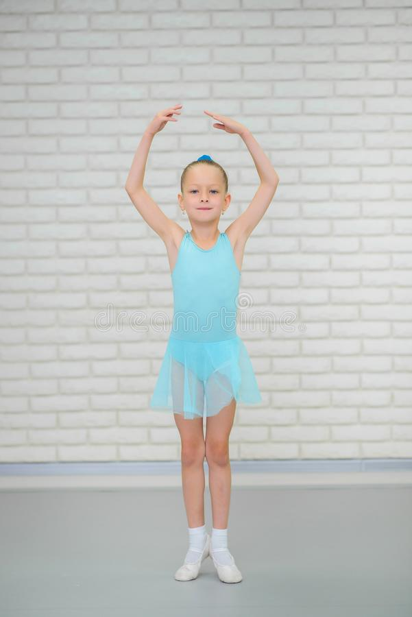 Little ballerina in blue dress and pointe shoes is dancing in ballet school. Cute girl in dance class. royalty free stock photos