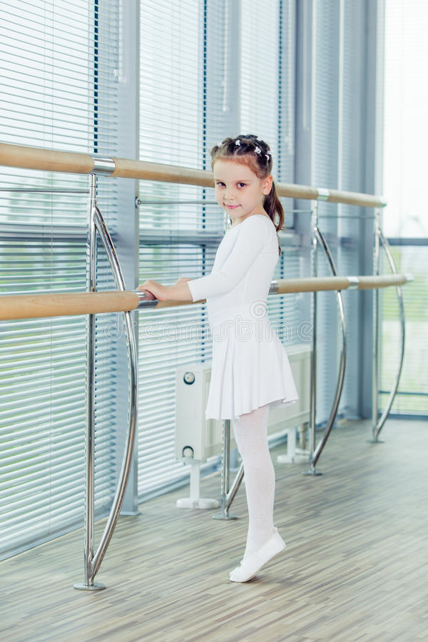 Little ballerina girl. Adorable child dancing classical ballet in a white studio. Children dance. Kids performing. Young gifted dancer in a class. Preschool royalty free stock image