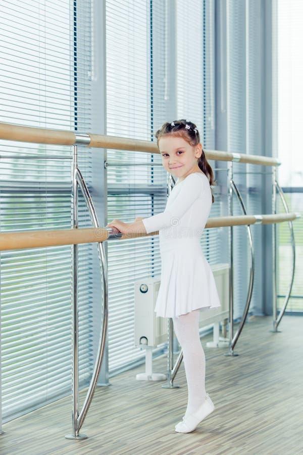 Little ballerina girl. Adorable child dancing classical ballet in a white studio. royalty free stock photos