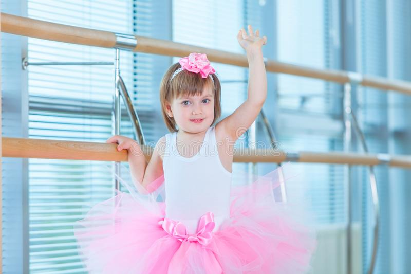 Little ballerina girl in a pink tutu. Adorable child dancing classical ballet in a white studio. Children dance. Kids stock photography