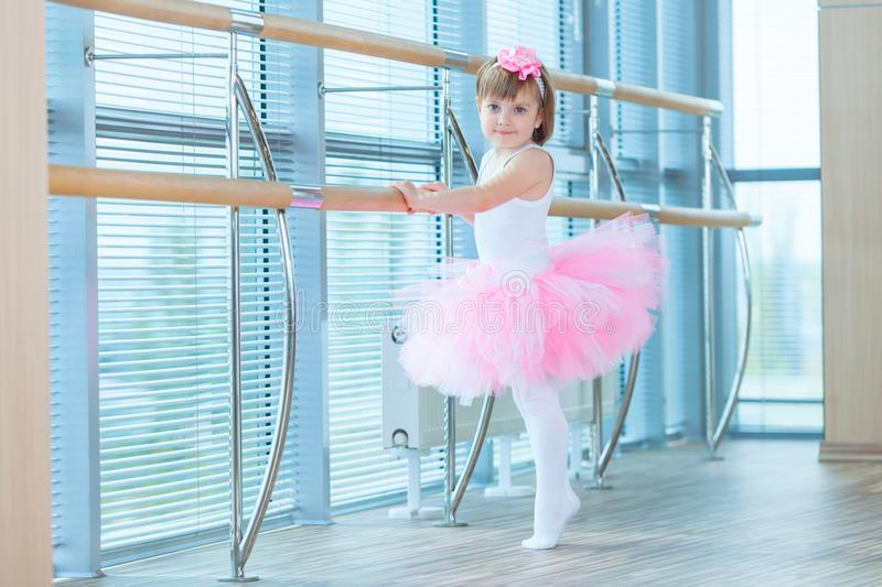 Little ballerina girl in a pink tutu. Adorable child dancing classical ballet in a white studio. Children dance. Kids royalty free stock images