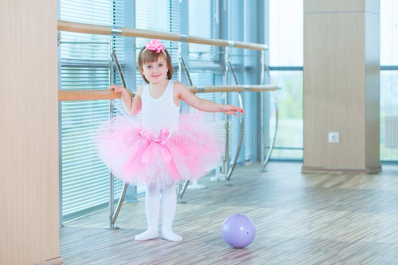 Little ballerina girl in a pink tutu. Adorable child dancing classical ballet in a white studio. Children dance. Kids stock photos