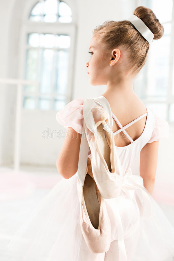 Little ballerina girl in a tutu. Adorable child dancing classical ballet in a white studio. stock image