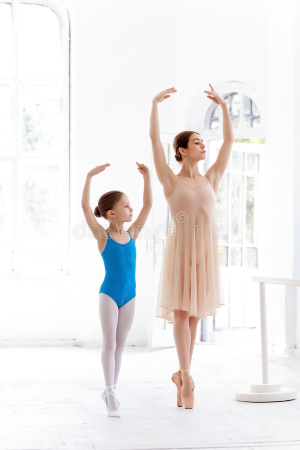 The little ballerina posing at ballet barre with personal teacher in dance studio stock photo