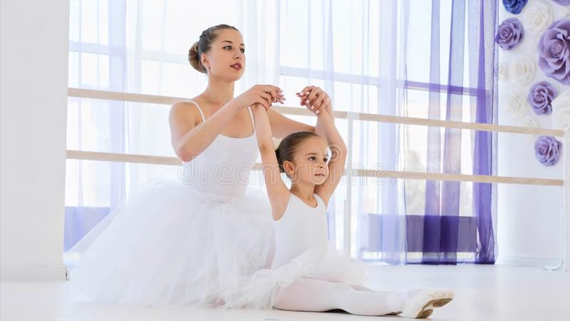 Little ballerina in white tutu is stretching on ballet lesson with teacher. royalty free stock images