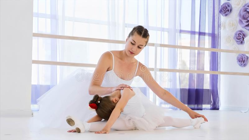 Little ballerina in white tutu is stretching with ballet teacher. royalty free stock photography