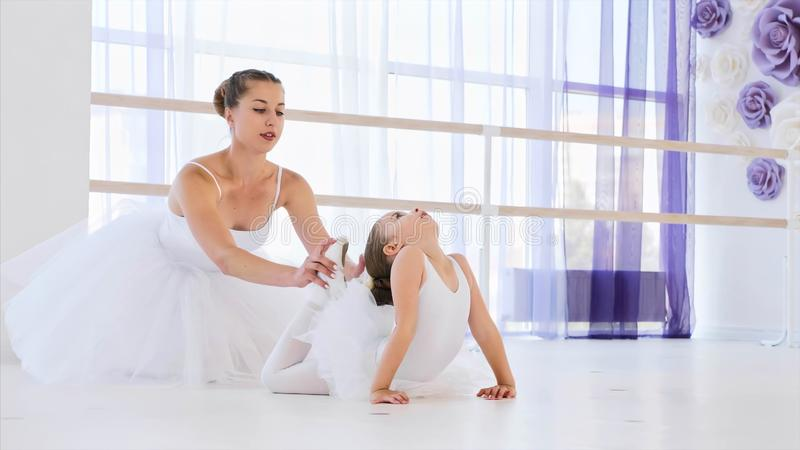 Little ballerina in white tutu is stretching in frog pose with ballet teacher. royalty free stock images