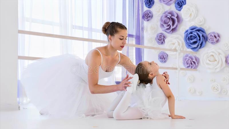 Little ballerina in white tutu is stretching in frog pose with ballet teacher. royalty free stock photography