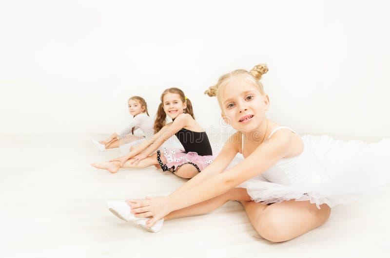 Little ballerinas sitting on floor of dance hall. Three little ballerinas, six years old girls in dancewear, sitting on the floor against blanked background of stock photos