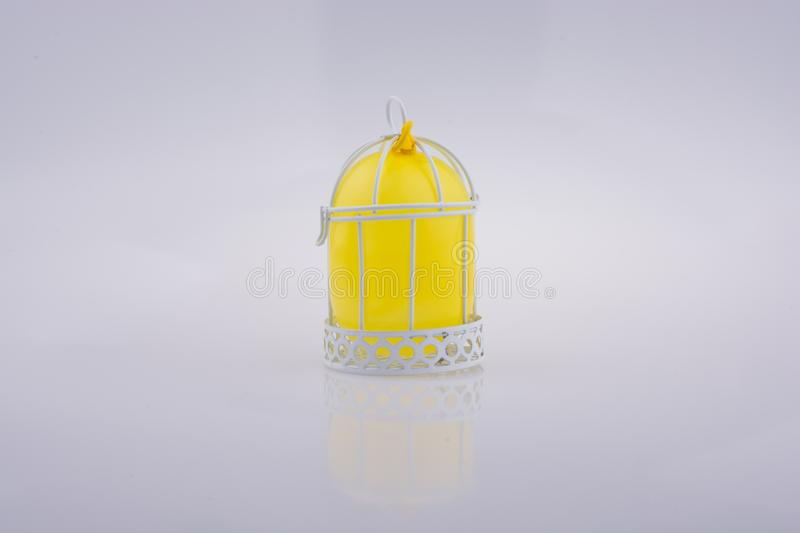 Little balloon placed in a white color bird house with metal bar. Little yellow balloon placed in a white color bird house with metal bars royalty free stock photos