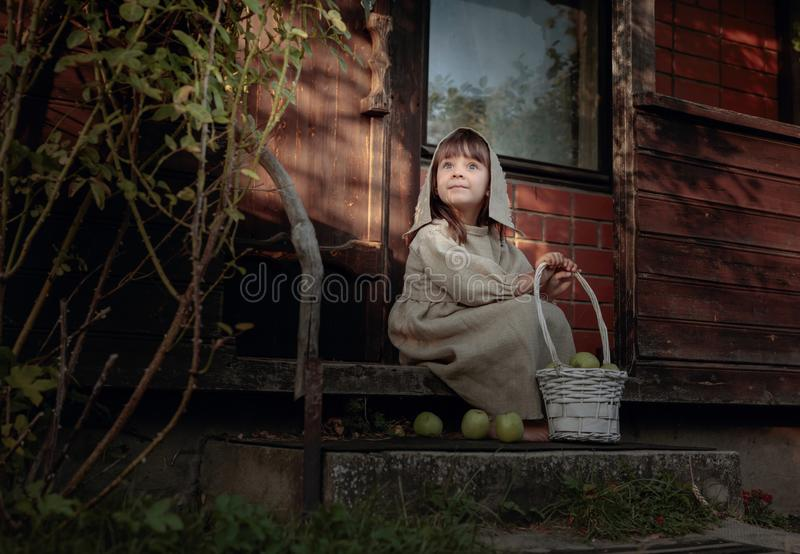 Dreaming girl with apples on a summer evening near the old house royalty free stock photo