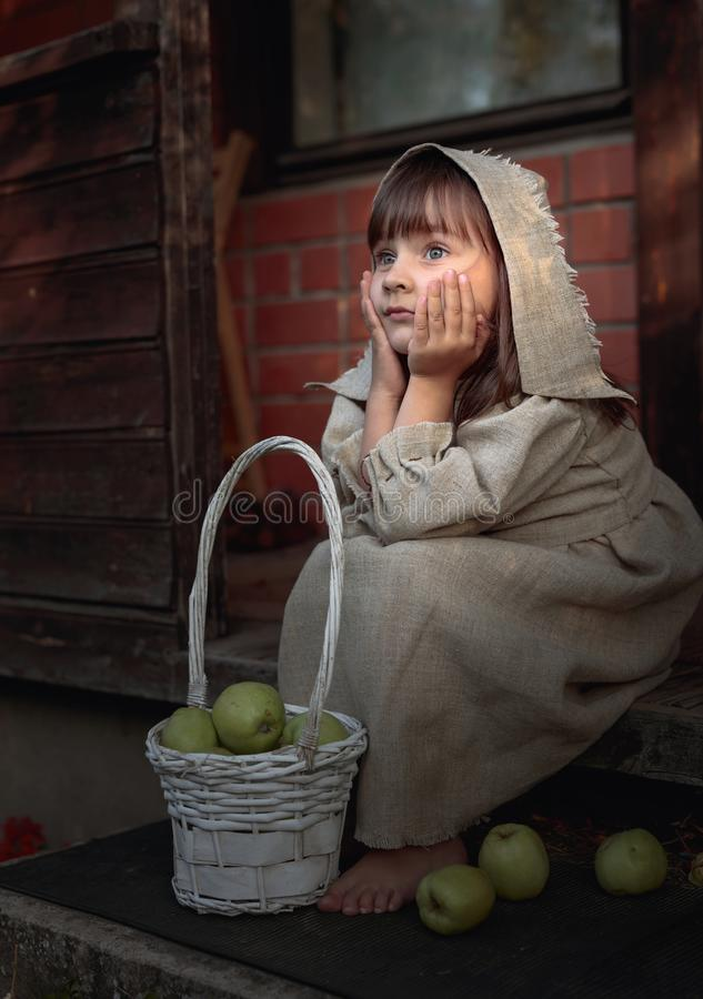 Dreaming girl with apples on a summer evening near the old house stock image