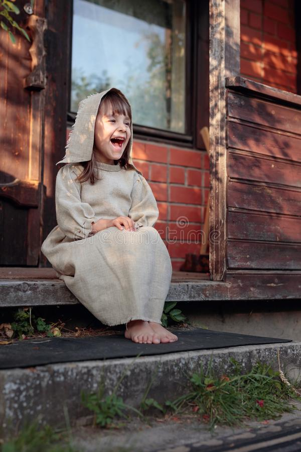 Little  barefoot girl in a old canvas dress on the threshold of the house royalty free stock image