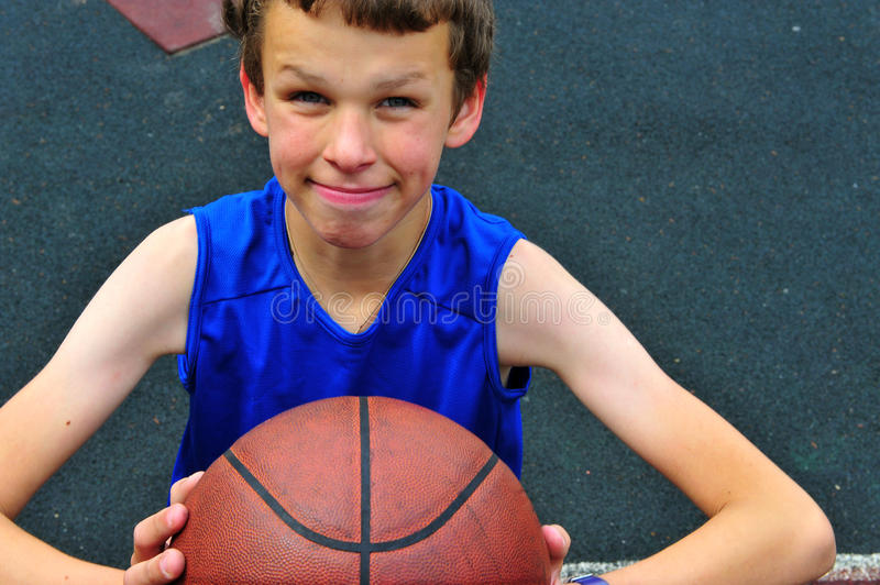 Little basketball player preparing for throwing ball on the court stock image