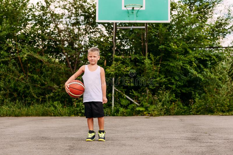 A little basketball player in a white t-shirt and black shorts stands with a ball on the basketball court in the summer royalty free stock images