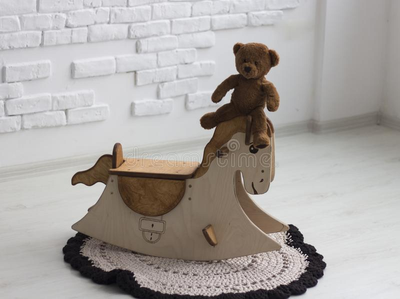 Little bear on the swinging horse royalty free stock photography