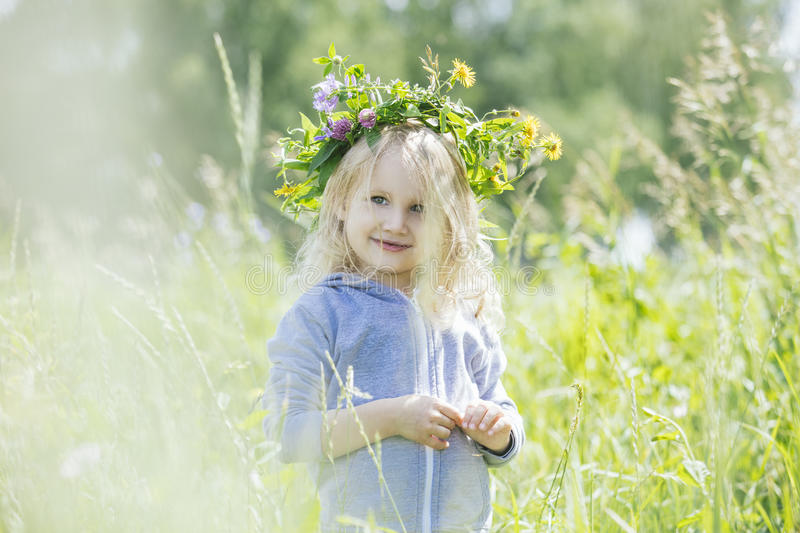 Little beautiful baby girl outdoors in a field in the fresh air royalty free stock photography