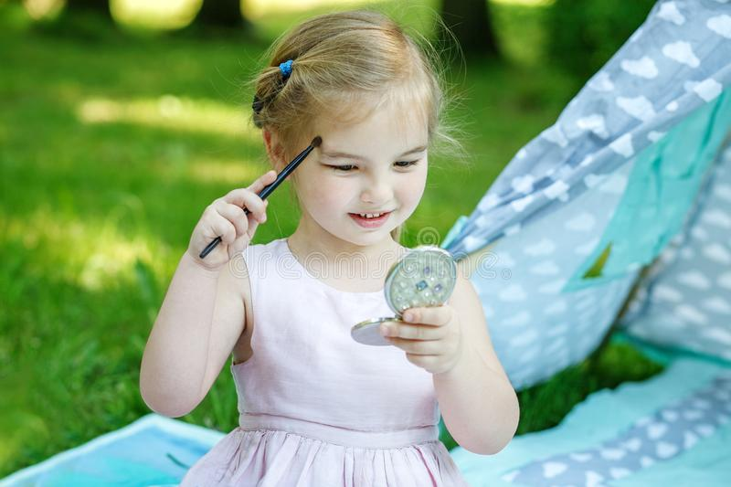 A little beautiful baby with a mirror. The girl is drawn with co stock photography