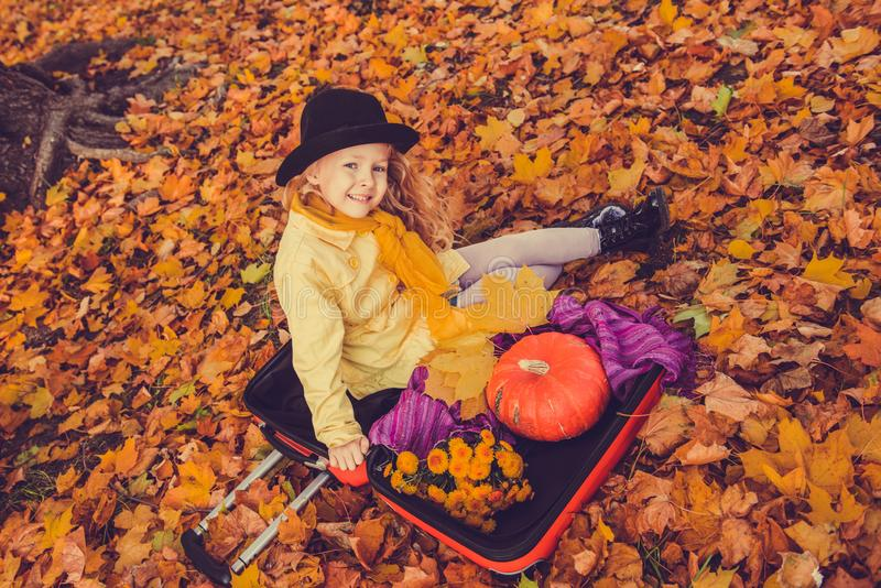 Little beautiful blond girl with big pumpkin in autumn background royalty free stock photography
