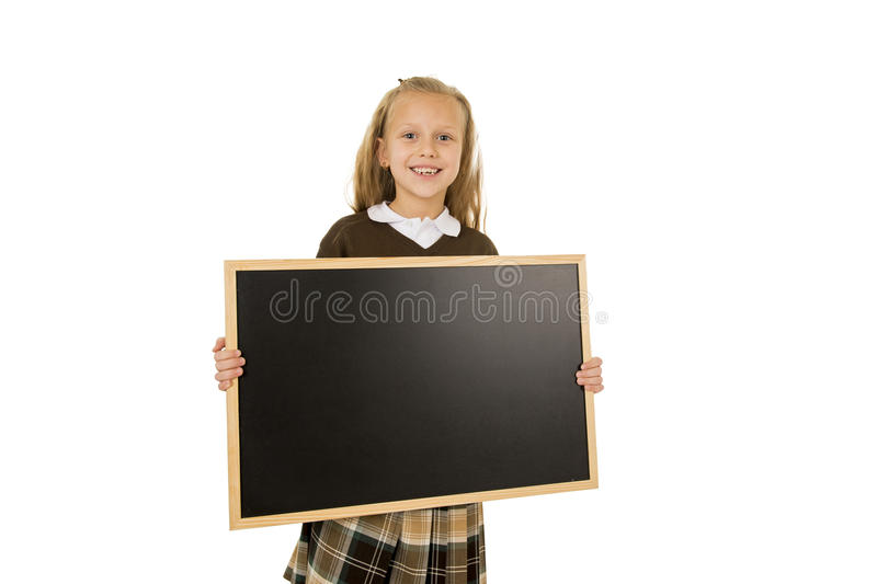Little beautiful blond schoolgirl smiling happy and cheerful holding and showing small blank blackboard royalty free stock images