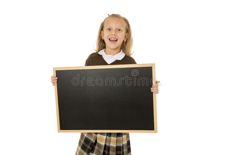 Little beautiful blond schoolgirl smiling happy and cheerful holding and showing small blank blackboard stock photography